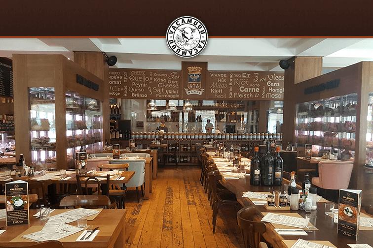 restaurant vacamuuu, cu doua randuri de mese de o parte si alta a restaurantului, mese si scaune din lemn, rustice, iar in fundal barul tot din lemn si tabla neagra pe care sunt scrise cu creta preparatele