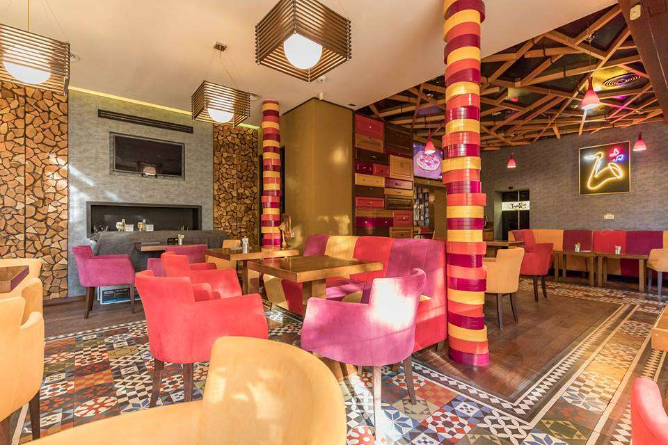 fotografie din restaurant retina by traffic, cu mese de 4 persoane si scaune tapitate in catifea roz, mov si crem, cu stalpi de sustinere colorati in aceleasi culori ca scaunele si bucati de perete cu mozaic auriu, iar podeaua este tot in stil de mozaic, cu model oriental, corpuri de iluminat patrate aurii, agatate de tavan