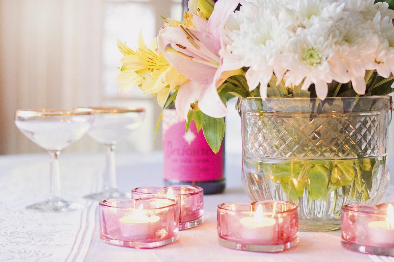 decor aranjat frumos, cu o vaza din sticla transparaneta, plina de flori, crizateme si crini, lumanari in suport de sticla roz, in forma de inima, o sticla de sampanie cu etichetta roz si doua pahare de sampanie, ca idee de marketing pentru Valentine's Day in restaurante