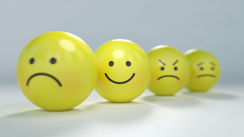 patru smiley-faces galbene, una vesela, alta suparata, alta trista si una furioasa, pe fundal gri, imagine reprezentativă pentru cum sa abordezi review-urile negative din online