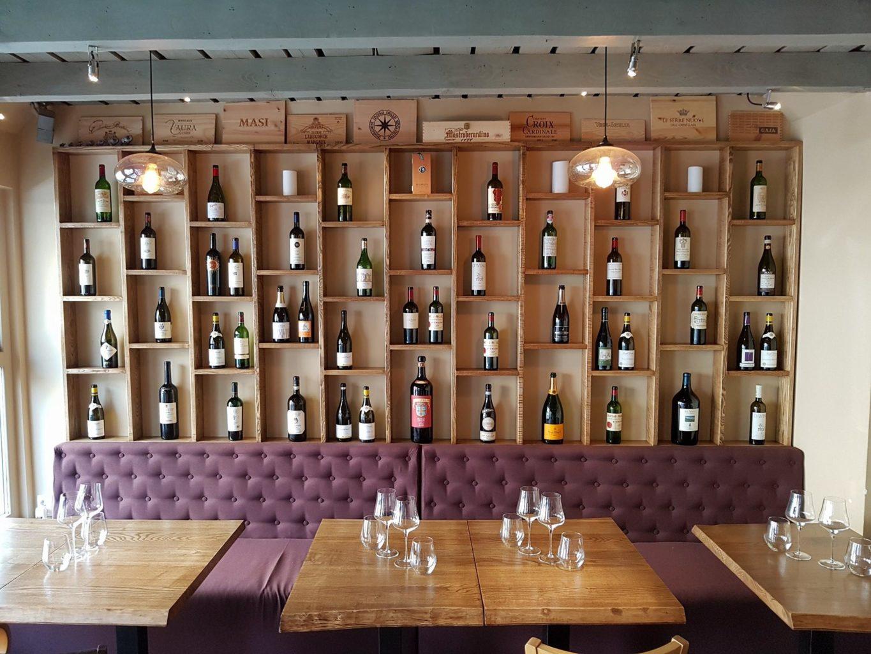 imagine din tasting room by ethic wine, in care se vede un perete intreg acoperit cu rafturi din lemn in care stau asezate sticle de vin, avand la baza o canapea mov, plusata, in fata careia stau asezate mese patrate de lemn, cu pahare goale de vin pe masa