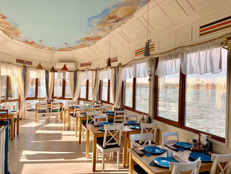imagine din taverna racilor herastrau, un restaurant mediteranean, amplasat intr-o barca pe apa, cu mese albe, podea de lemn, scaune albe cu sezut tapitat albastreu, ferestre de jur imprejur, cu perdelute si u tavan bleo