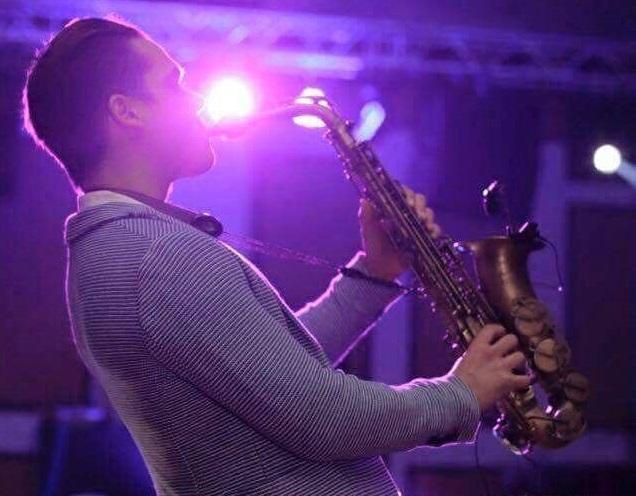 barbat fotografiat din profil,  cantand la saxofon, imbracat in costum, intr-o camera iluminata difuz, iar in fundal se vad reflectoare de scena suspendate