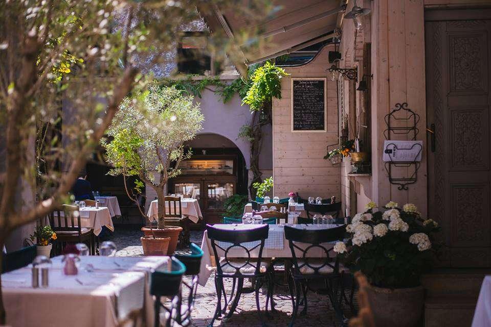 gradina exterioara de la restaurantul white horse, o gradina interioara a unei vile, cu scaune din fier forjat asezate la mese si ghivece mari cu maslini, care decoreaza curtea