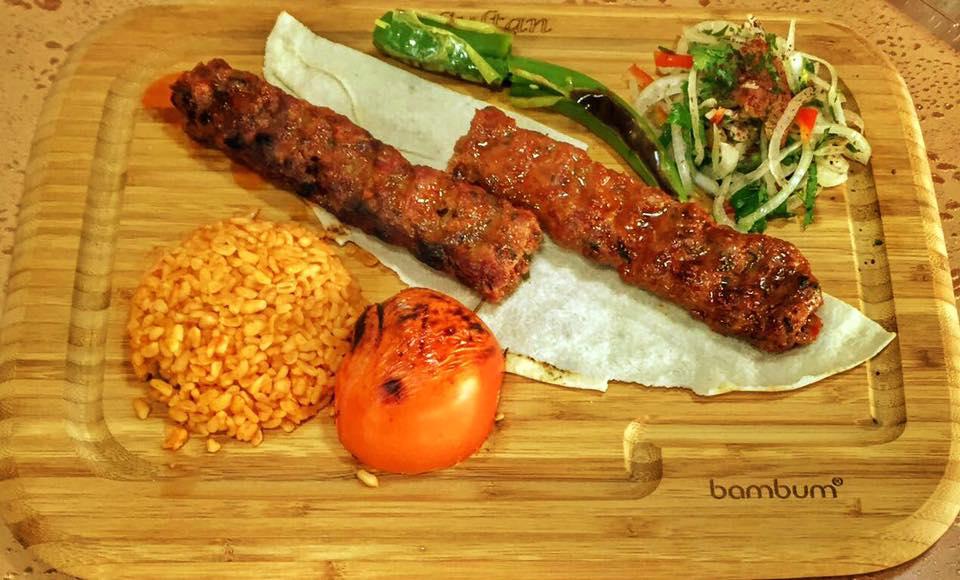 preparat din restaurant by sultan, doua bucati de kebab servite pe un platou de lemn, impreuna cu bulger si rosie pe gratar, unul din cel mai bun kebab din bucurești