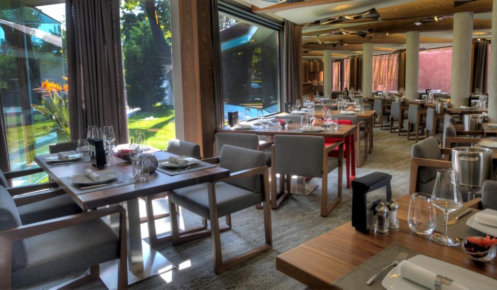 imagine din restaurant casa di david, cu un salon circular cu perete de sticla si mai multe mese de patru persoane, unul din restaurante fine dining bucurești