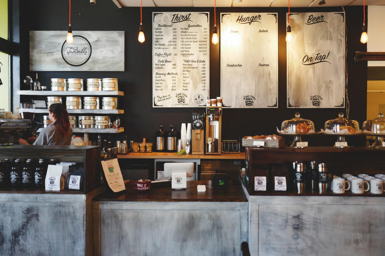 imagine cu barul unui restaurant, cu pereti negri pe care sunt afise albe, rafturi cu recipiente metalice, cesti de cafea cafetiere, imagine reprezientativa pentru situatia provocata de coronavirus in restaurante