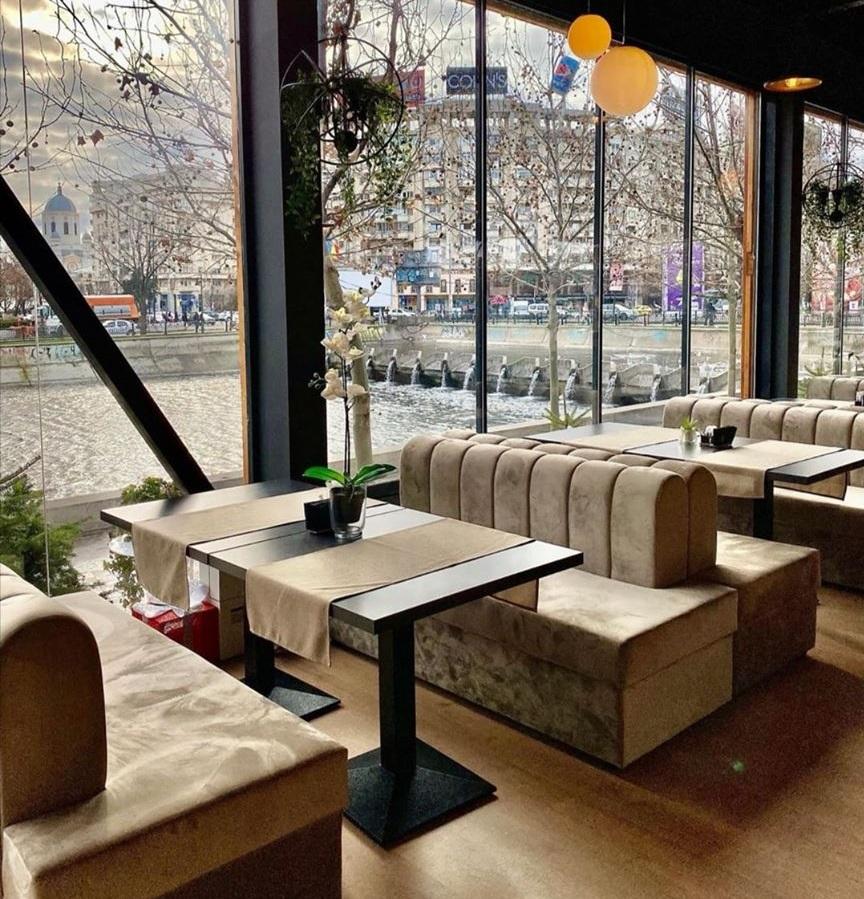 imagine din colonial lounge cafenea de la Uniri, in care se vad mai multe canapele asezate fata in fata, cu mese intre ele, plusate, crem, cu mese deschise la culoare, asezate in dretul unor ferestre mari cu vedere la raul Dambovita