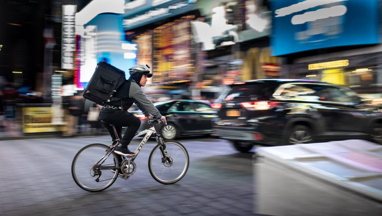 curier care duce o comandă de mâncare acasă, pe bicicleta, in oras aglomerat cu masini trecand pe langa el, noaptea