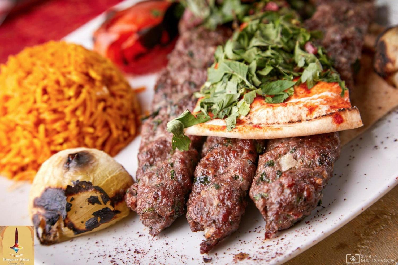 close up cu o farfurie din damascus palace restaurant, cu trei bucati de kebab servite pe farfurie alba, cu verdeata, lipie, bulguri si ceapa pe gratar