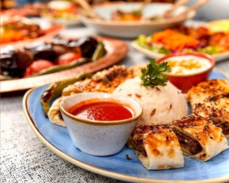 close up din restaurant Divan, cu o farfurie din ceramica albastra pe care sunt asezate felii de Sarma Beyti, cu o cescuta de sos rosu si orez in mijloc, unul din cel mai bun kebab din București