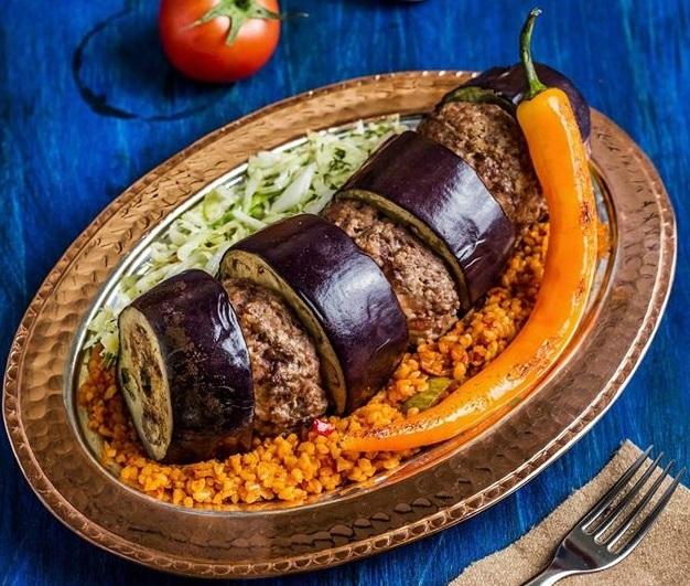 close uo din restaurant efes turkish cuisine concept, cu un platou de paltican kebab, cu vinete umplute cu carne tocate, servite cu salata si ardei iute, platou fotografiat pe fundal albastru