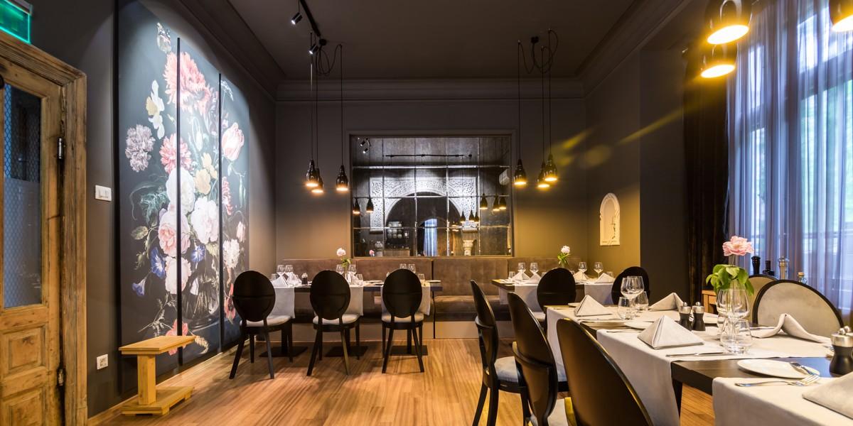 imagine de ansamblu dintr-o incapere a restuarantului joseph by joseph hadad, camera iluminata difuz, cu picturi pe peretele stang, mese de 6 persoane cu scaune cu spatar rotund, canapele in fundal si oglinzi pe peretele din fata