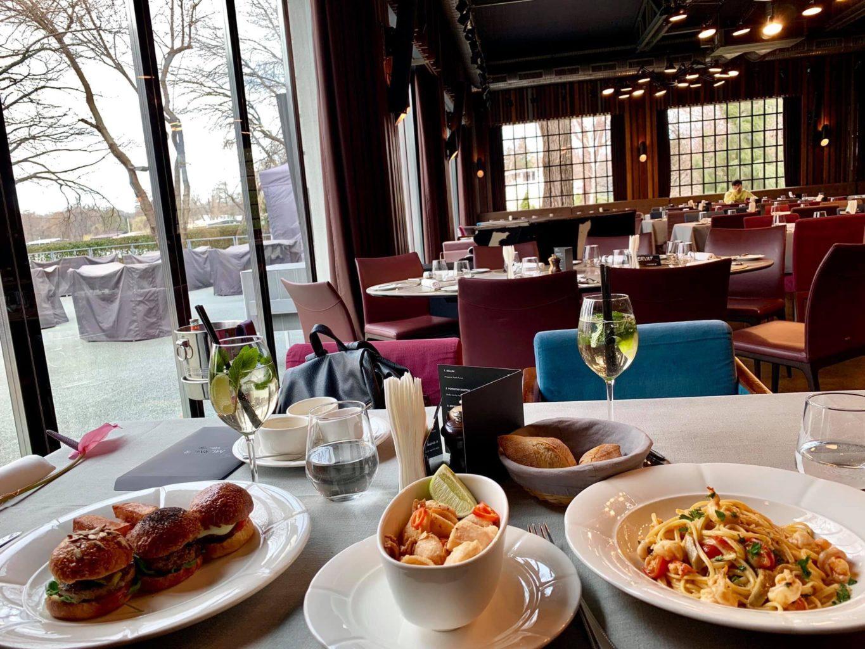 prim plan cu o masa din restaurant la brasserie bistro & lounge, asezata langa un perete din sticla, iar in fundal sunt alte mese, scaune capitonate cu rosu si ferestre