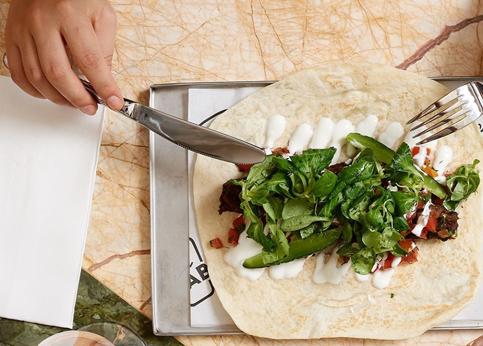 close up din restaurant Le Bab, cu o tavă metalica asezata pe o masa din marmura, pe care este servita o lipie cu carne, verdeata si sos, unul din cel mai bun kebab din București