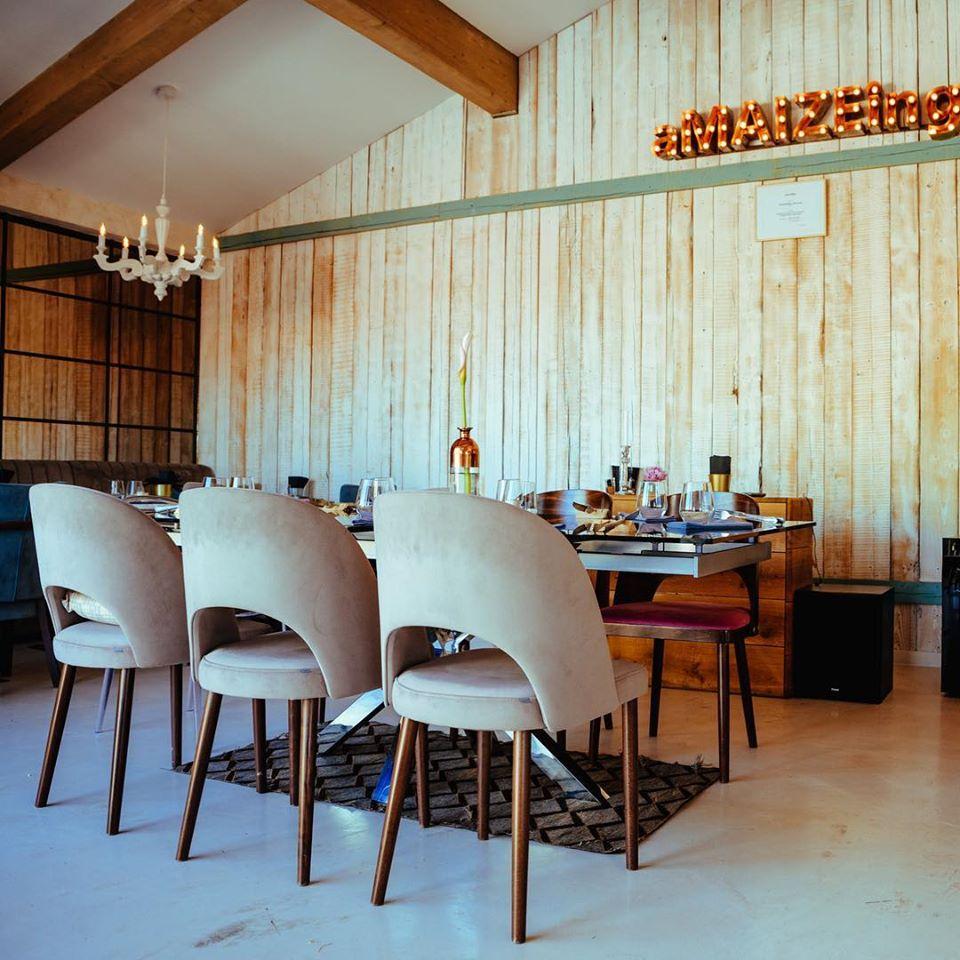 imagine din restaurant maize farm to table, cu o masa de 6 scaune in prim plan, cu scaune confortabile, crem, un perete din lemn in fundal cu semn luminos amazeing si un candelabru de tavan, unul din restaurante fine dining bucuresti