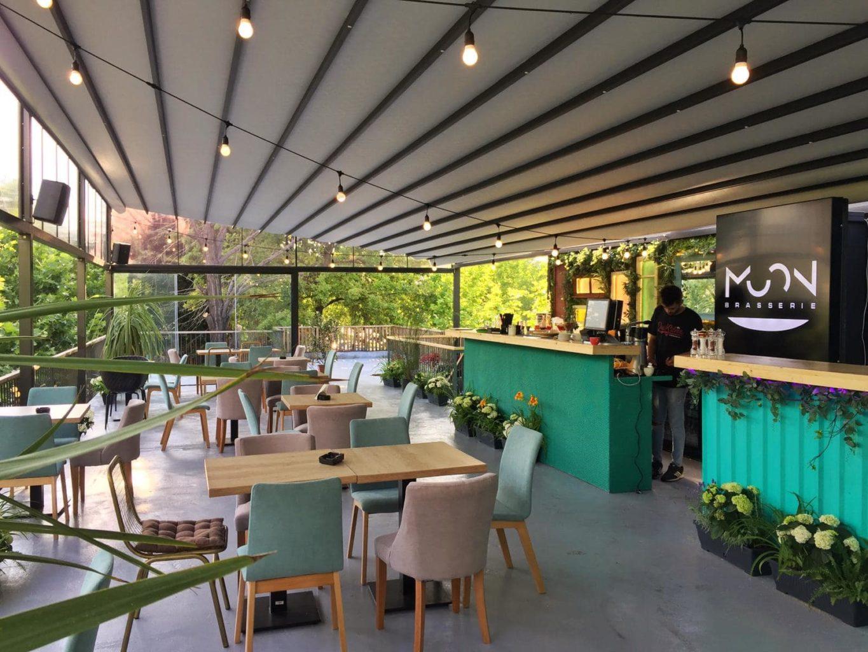 privire de ansamblu din moon brasserie una din cafenele de la Unirii, cu doua laturi formate din ferestre mari, mese de 6 persoane, din lemn, cu scaune tapitate in crem si vernil, si un bar verde in partea dreapta