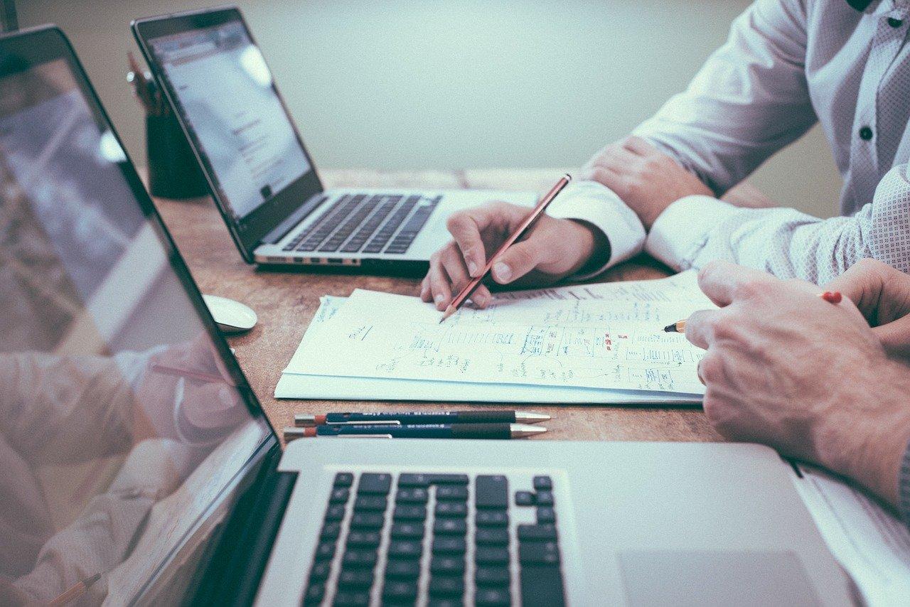 close up cu doua laptopuri si mainile a doua persoane care fac calcule pe hartii a4, imagine sugestiva pentru cum poti obține Certificatul de Situație de Urgență