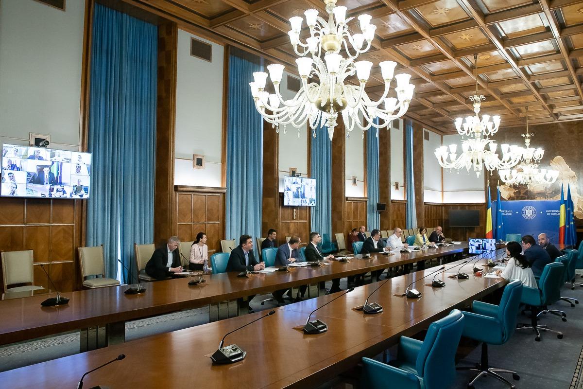 sedinta de guvern din 18.03, din sala mare de sedinte, cu 2 mese lungi din lemn la care sunt asezate ministri, candelabru mare, draperii lungi albastre la geamuri. Seinta in care s-a hotarat ca statul sa sprijine HORECA