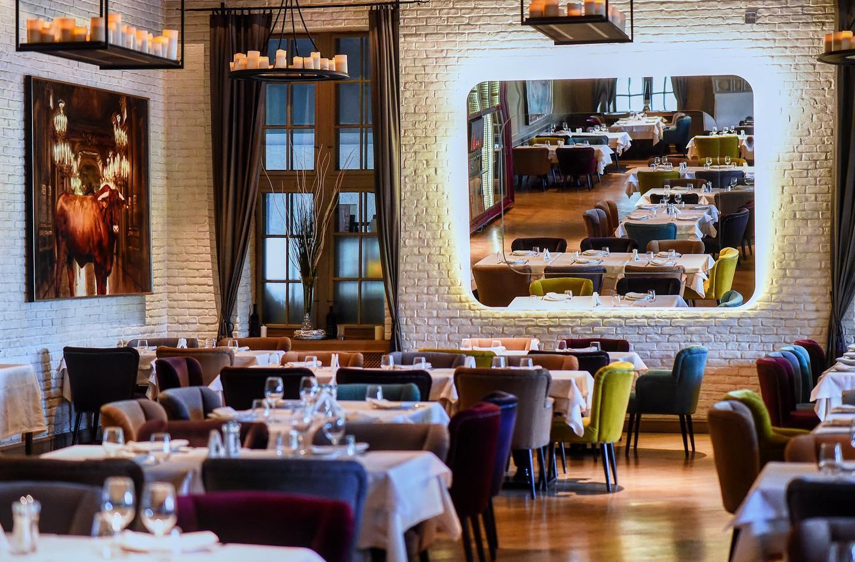 imagine din restaurant diplomat, cu sala de mese eleganta si un perete din caramida vopsit in alb, pe care este amplasata o oglinda mare in care se refkecta mesele din restaurant, unul dinrestaurante fine dining bucurești