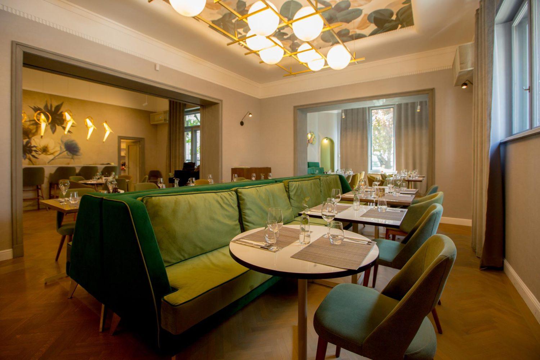 imagine din restaurant savart, cu o canapea mare, verde, in prim plan, in fata careia sunt asezate mese si scaune, un candelabru modern pe tavan, si in fundal o alta incapere cu un perete pictat si ferestre mari in fundal, unul din restaurante fine dining bucurești
