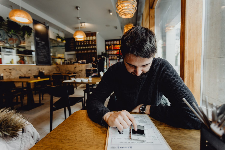 barbat stand la masa in restaurant gol, cu capul plecat, uitandu-se in telefom, imagine reprezentativa pentru restaurantele afectate de coronavirus