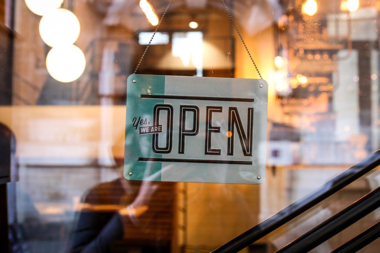 semn de magazin agatat de usa, pe care este scris negru pe alb open, imagine reprezentativa pentru restaurante deschise in perioada de coronavirus