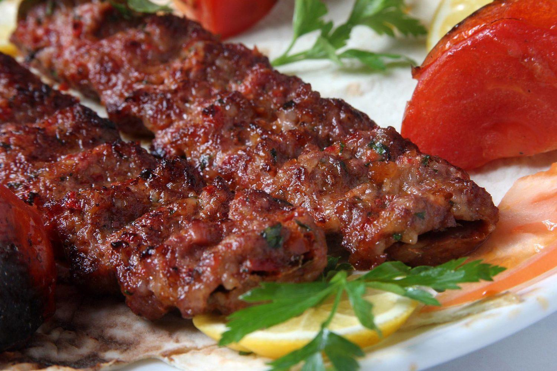 close up din Saray Restaurant, cu doua bucati de kebab facut pe gratar, asezate pe farfurie alba cu frunze de patrunjel si o bucata de rosie in fundal, unul din cel mai bun kebab din bucurești