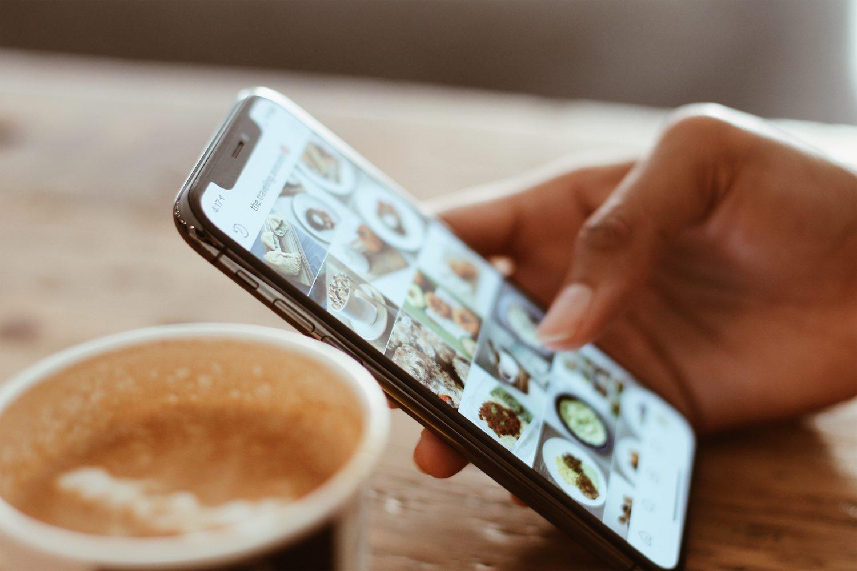 focus pe un telefon tinut in mana, cu cineva care navigheaza poze, imagine sugestiva pentru restaurante de la care poți comanda mâncare acasă