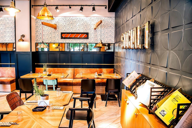 social 1 una din cafenele de la unirii, cu mese din lemn, canapele din piele portocalie, tapet alb, corpuri aurii suspendate de tavan, oglinda prinsa pe perete si un perete negru in dreapta