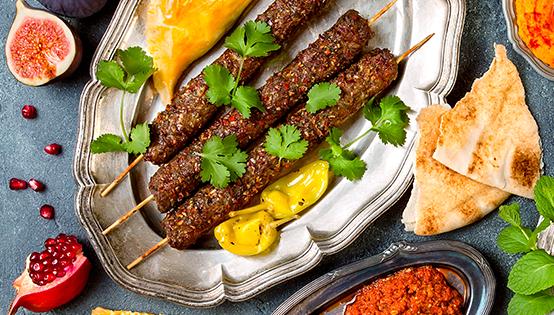 fotografie din restaurant turqoise, cu o tava metalica asezata pe fundal albastru, pe care sunt servite trei frigarui cu kebab, asezonat cu verdeata si doi ardei iuti, iar langa tava se afla o felie de rodie, sochina, lipii si o farfurie cu sos rosu