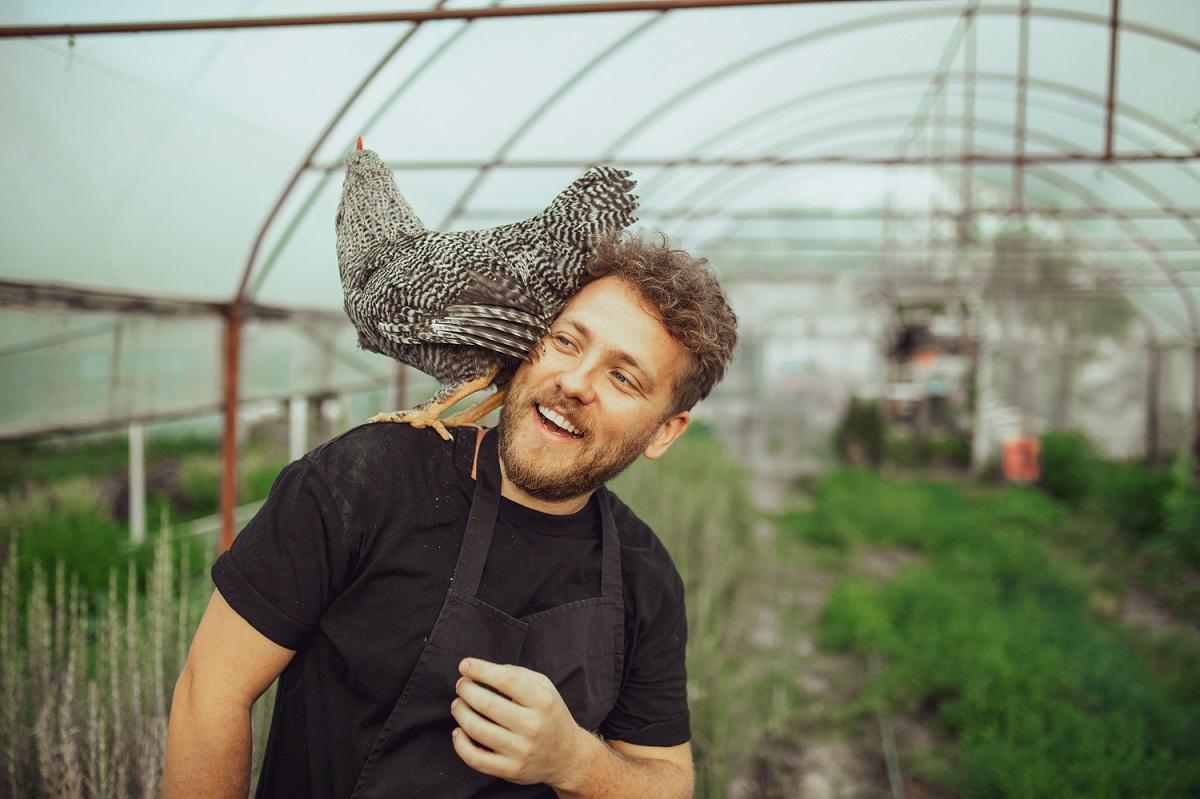 chef Alexandru Iacob de la restaurant MAT, fotografiat intr-o seră, cu o gaina pe umar
