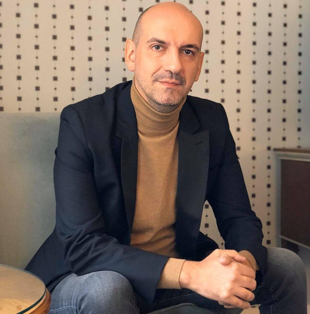Dani Caramihai, CEO Fratelli Grup, despre criza dinr estaurante provocate de Covid-19., fotografiat stand pe fotoliu, cu mainile impreunate pe genunchi, imbracat in sacou albastru si bluza crem