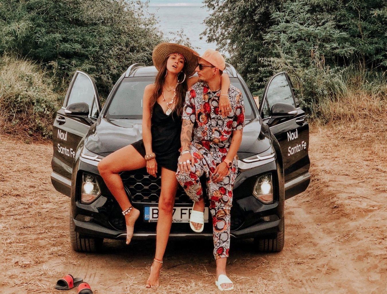 imagine pentru interviu Fabuloasa și Otravă, cu Diana Enciu și Cristian Șimonca fotografiați pe bordul unei masini negre, cu portierele deschise, purtand palarii si stand unul langa altul, vara