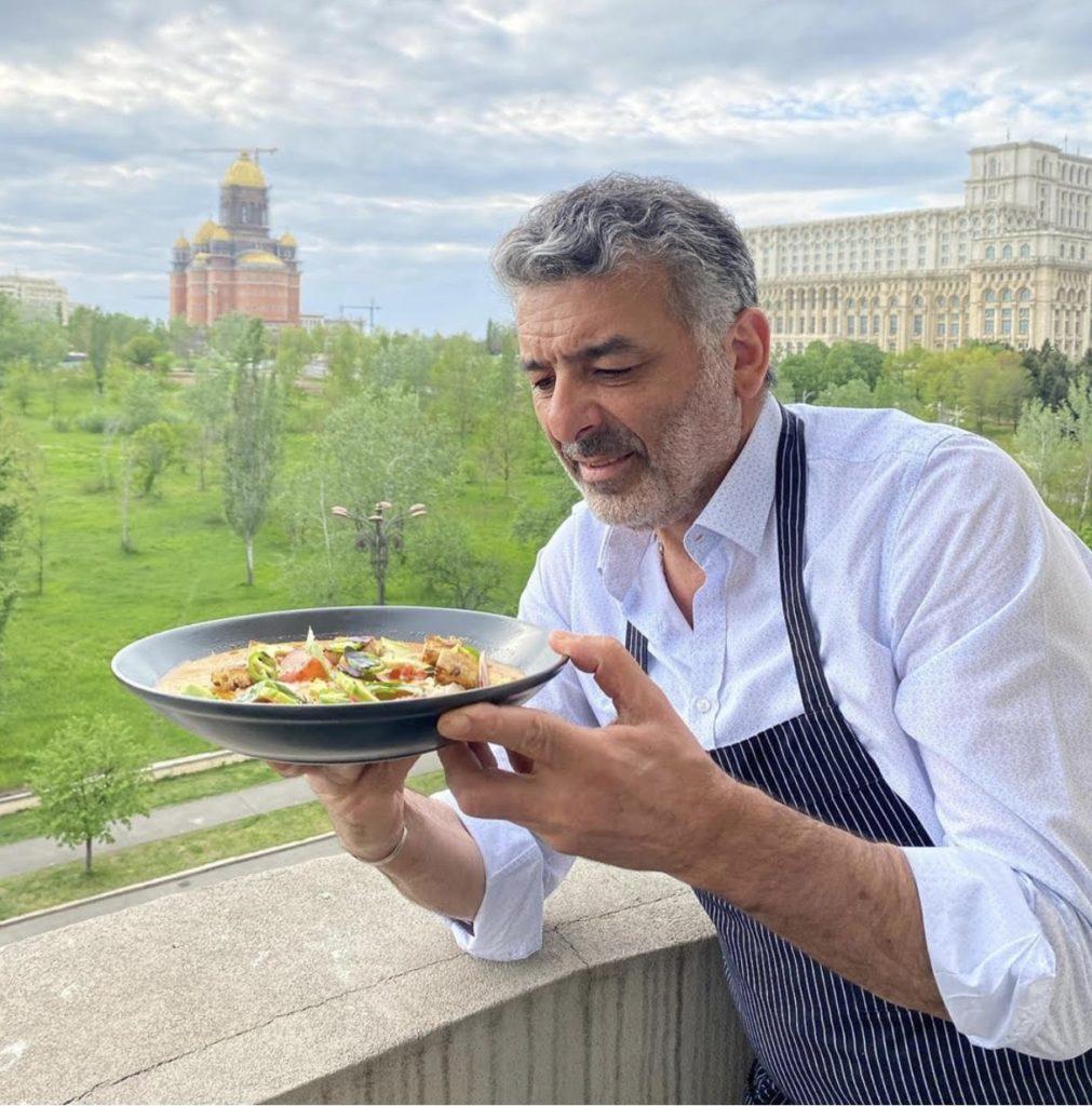 chef joseph hadad fotografiat pe balconul sau de acasa, cu sort de bucatar si o farfurie cu mancare in maini