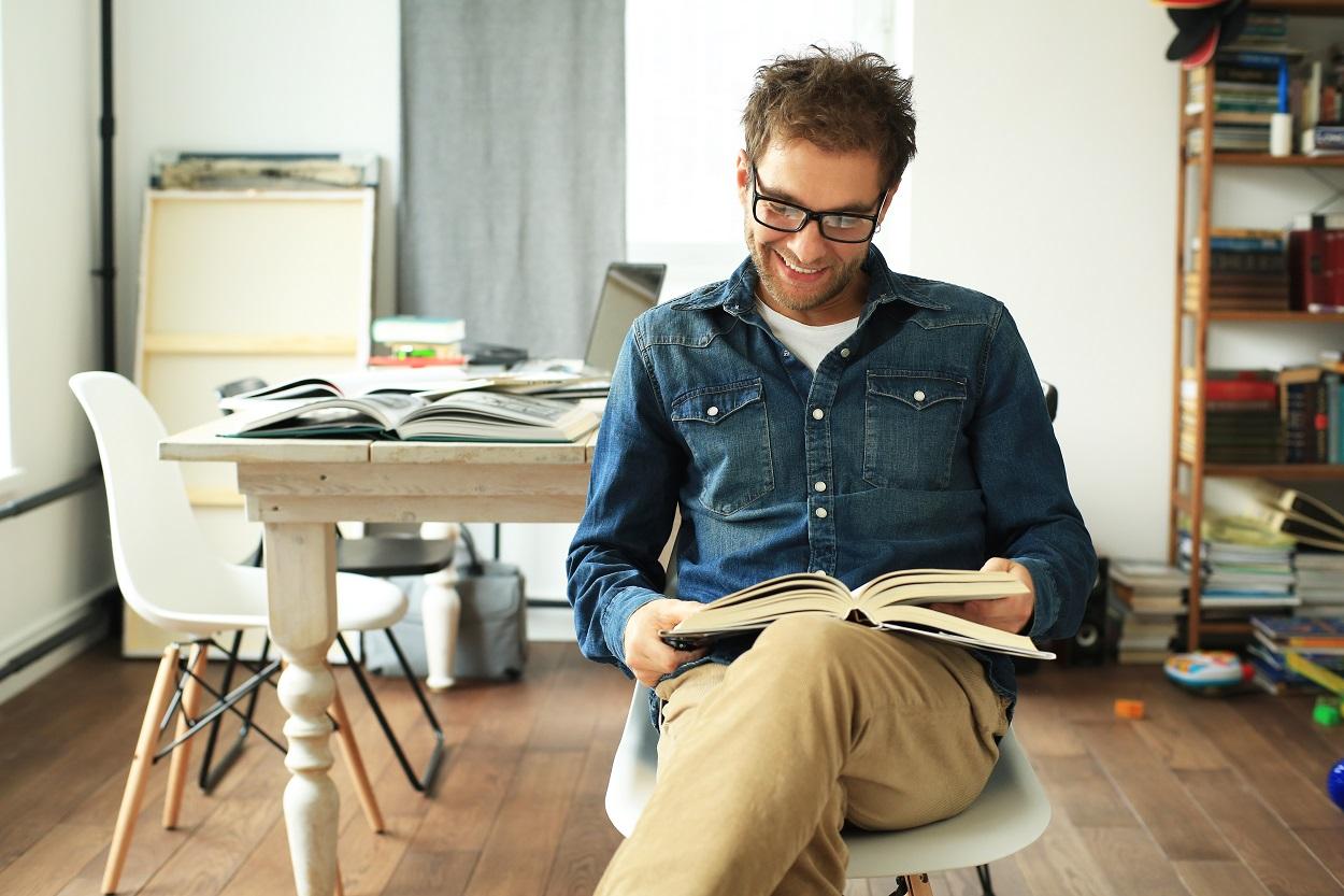 barbat tanar cu ochelari citind cărți de dezvoltare personală, așezat pe un scaun, cu mobilă în fundal, imbracat cu camasa albastra de blugi