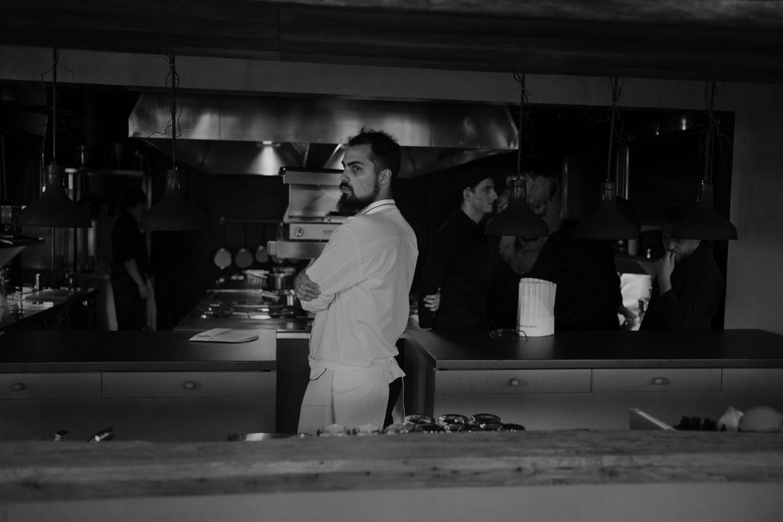 chef radu ionescu in bucataria restaurantului kaiamo, in uniforma de bucatar, privind in lateral. foto alb negru