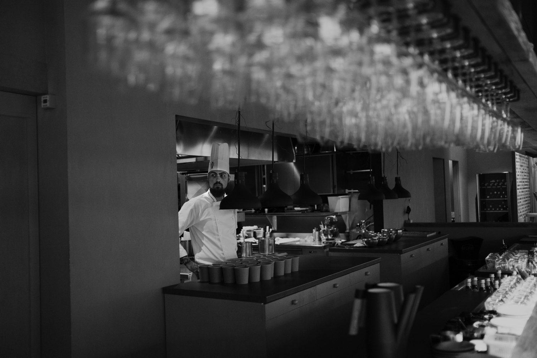 chef radu ionescu in bucataria restaurantului kaiamo, imagine de ansamblu cu barul plin de pahare suspendate, foto alb negru