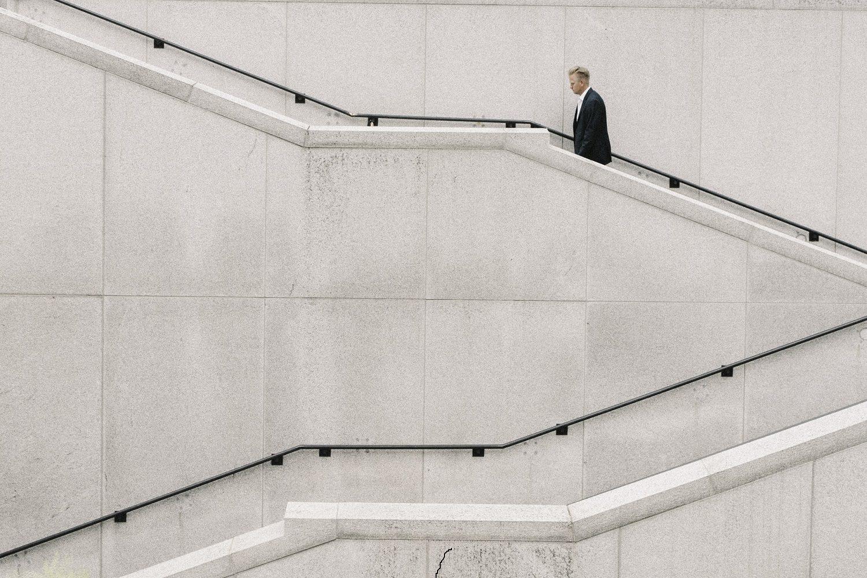 om de afaceri in costum negru, urcand singur pe trepte albe, fotografiat de la distanta, imagine reprezentativa pentru cum va arata lumea după pandemia COVID-19