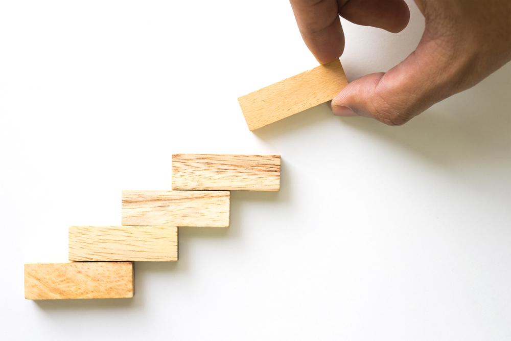 blocuri de lemn pe o coala alba, reprezantand imaginea de scara care te duce catre succes si leadership