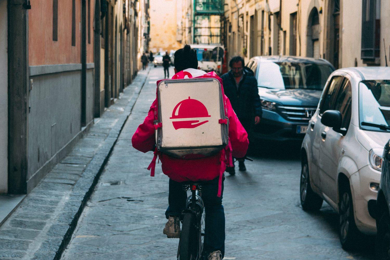 barbat care face livrari, delivery,pe bicicleta, cu o geanta termoizolanta in spate, imagine reprezentativa pentru măsuri de siguranță la livrări și takeout
