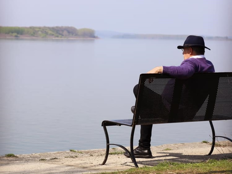mircea dinescu asezat pe o banca, pe malul dunarii, fotografiat de la distanta, din semi profil