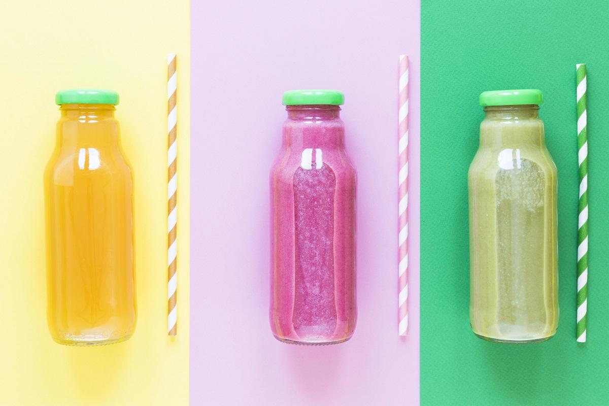 trei sticle de smoothie sănătos, cu capac verde, pe fundal colorat, cu cate un pai langa fiecare