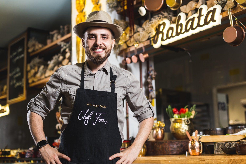 chef foa, florin scripcă, flavours, imbracat in camasa so sort negru de bucatar, cu palarie in cap, fotografiat in restaurant