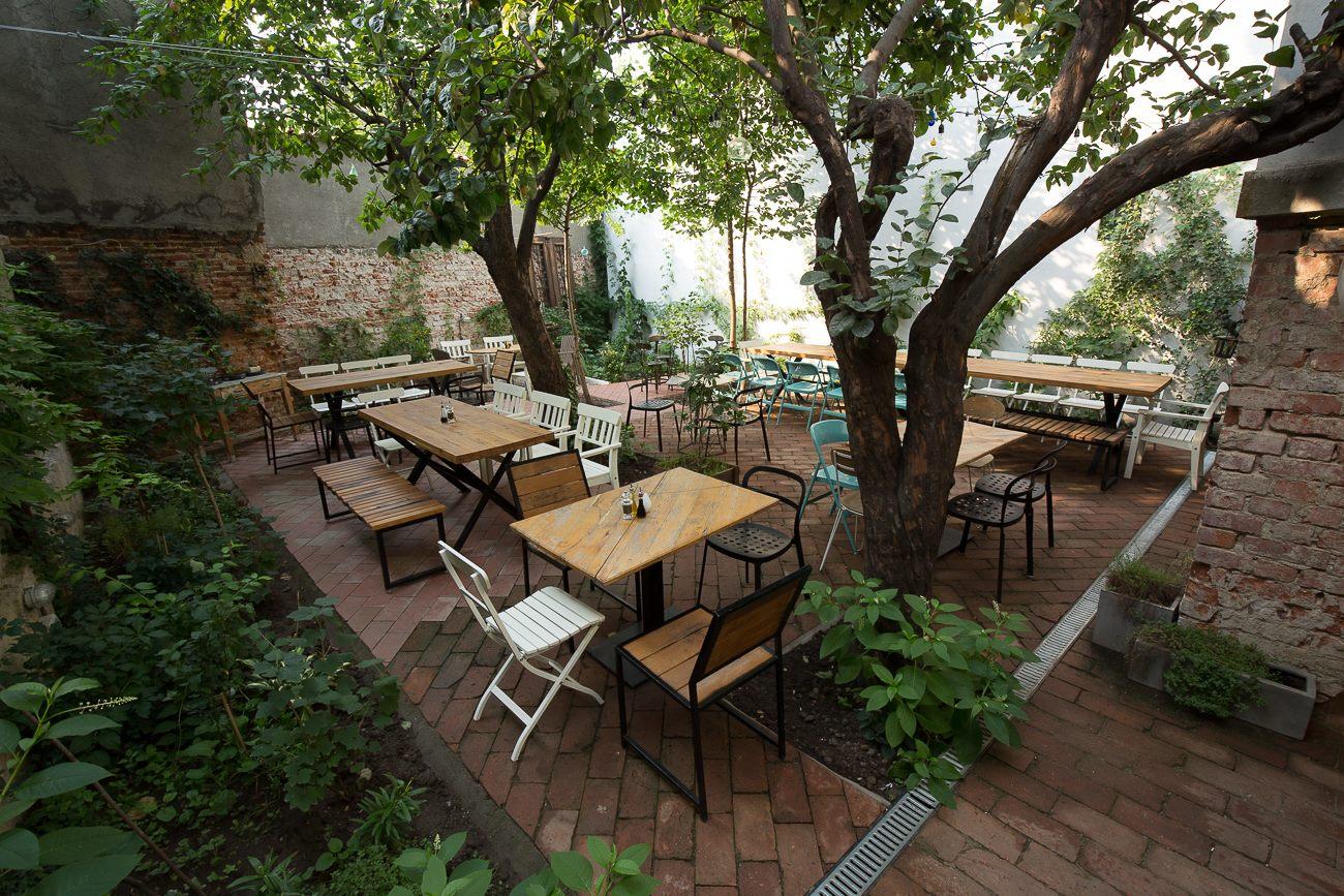 Grădina restaurantului Simbio din Bucuresti, cu mese goale, printre copaci