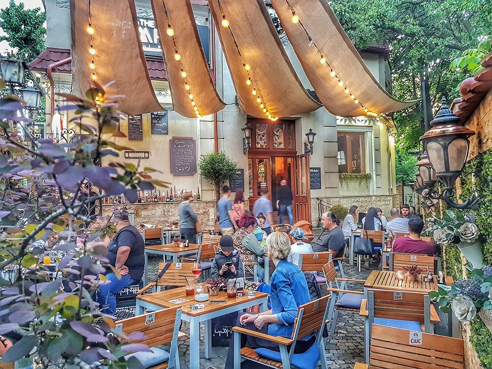 terasa plina cu oameni asezati la mese, cu o casa boiereasca in fundat si copertina cu beculete deasupra meselor, la The Temple Social Pub
