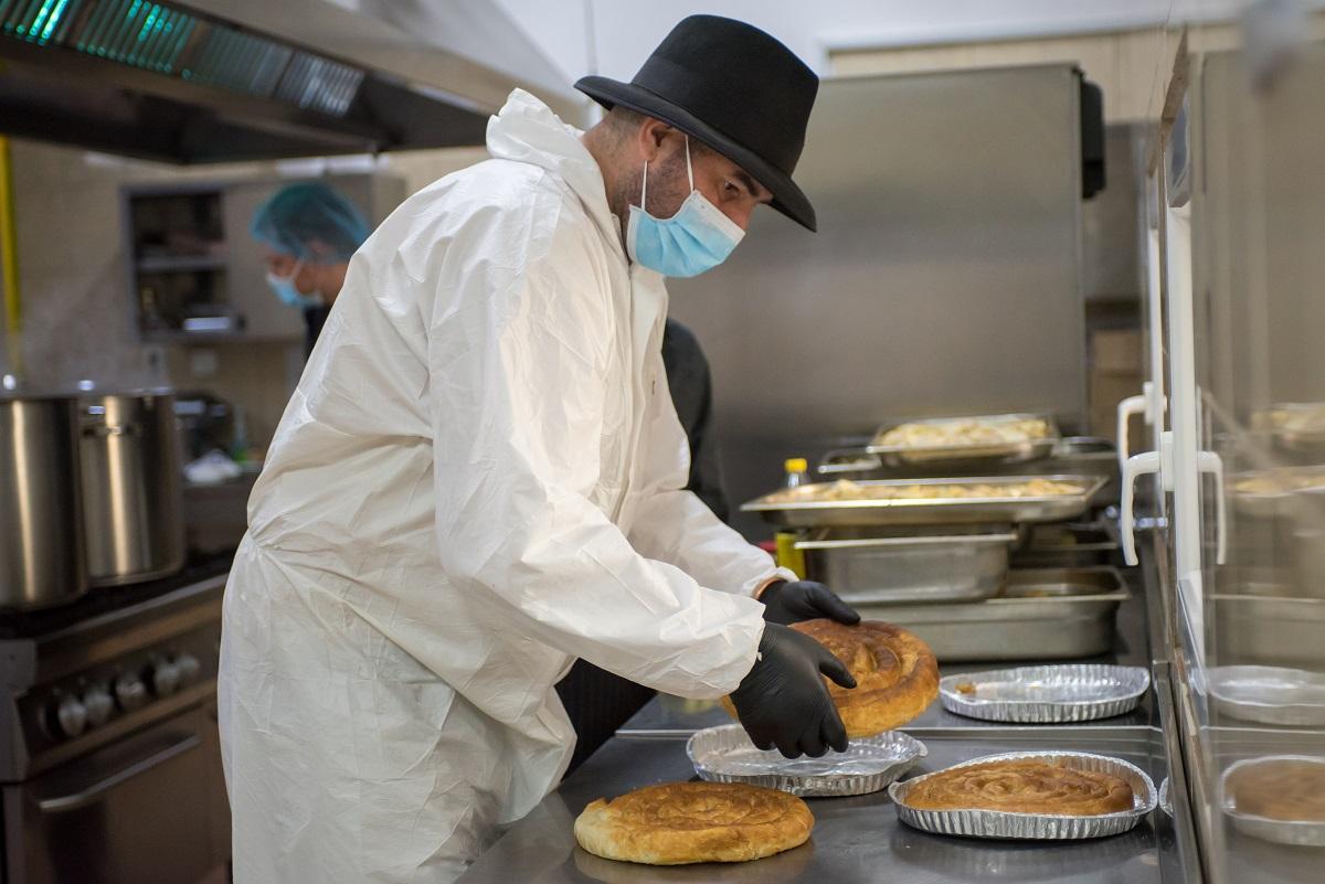 Chef Adi Hădean in combinezon anti covid-19, gatind in bucătărie pentru proiectul Solidar Social