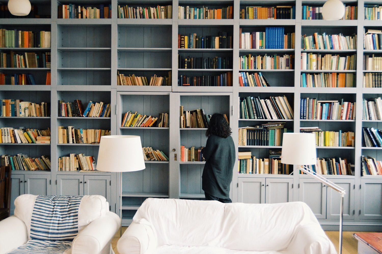 gata in fata unui perete plin cu rafturi de biblioteca si carti, imagine reprezentativa pentru (auto)biografii pe care să le citești