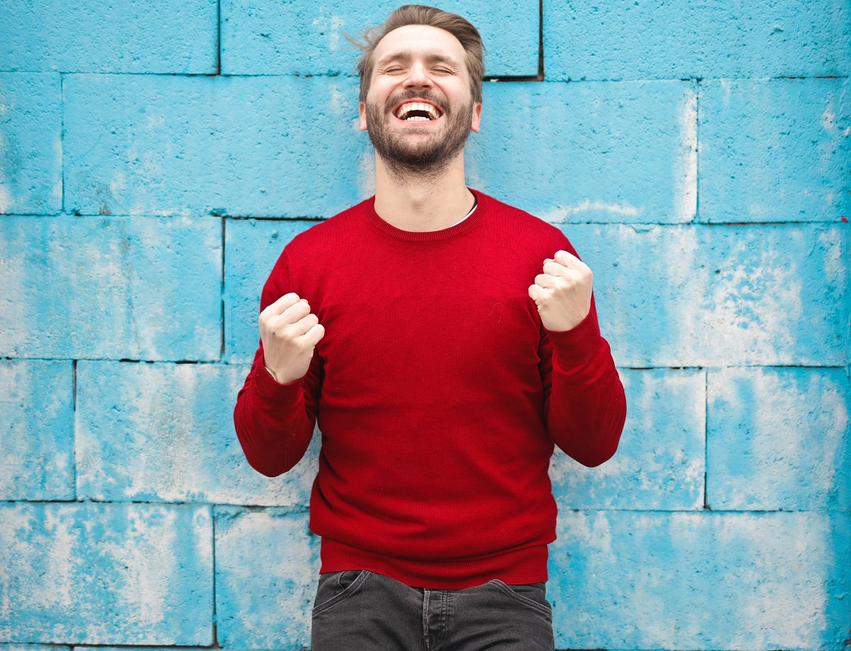 barbat in pulover rosu, in fata unui pereta albastu, barbat din categoria oamenilor norocosi