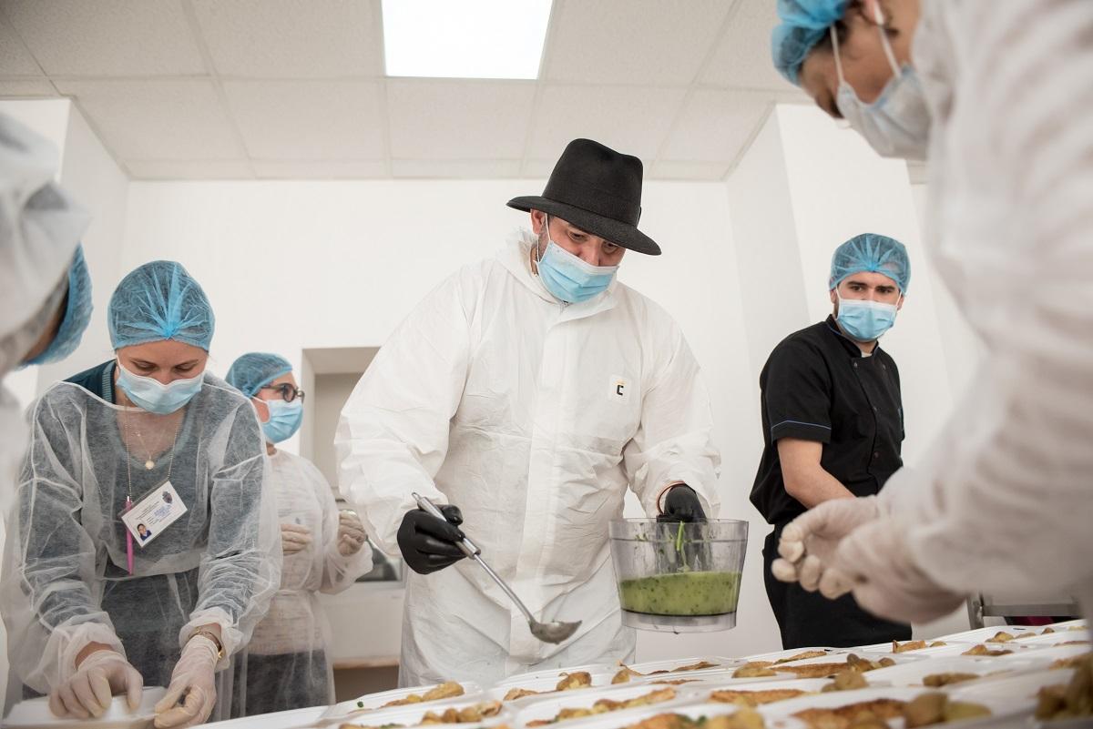 Chef Adi Hădean in costum de protecție împotriva coronavirus, gatind in cadrul proiectului Solidar Social